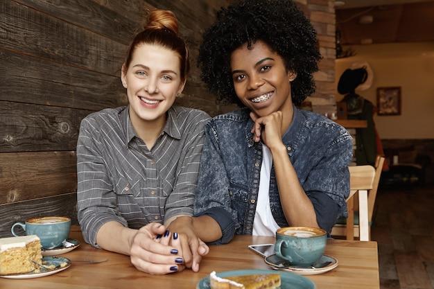 Homosexuelle partnerinnen von samesex trinken kaffee und essen kuchen im restaurant Kostenlose Fotos