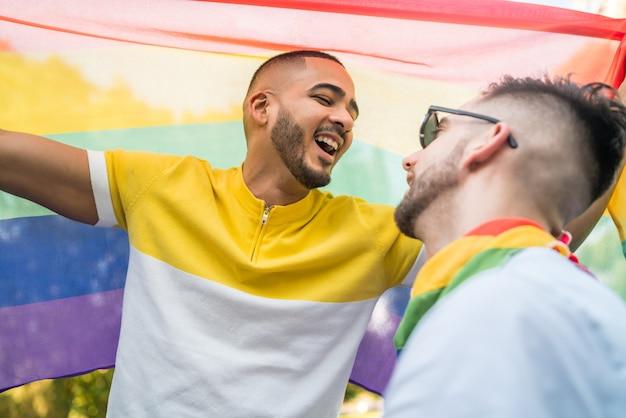 Homosexuelles paar, das ihre liebe mit regenbogenfahne umarmt und zeigt. Kostenlose Fotos
