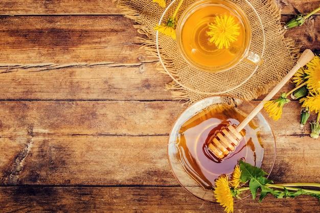 Honig aus löwenzahn und einer tasse tee. selektiver fokus Premium Fotos