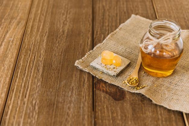 Honig; bienenblütenstaub und -bonbons auf sackstoff über hölzernem hintergrund Kostenlose Fotos