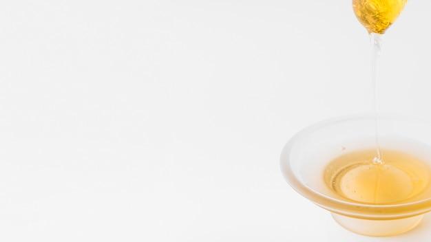 Honig, der in schüssel vom schöpflöffel auf weißem hintergrund tropft Kostenlose Fotos
