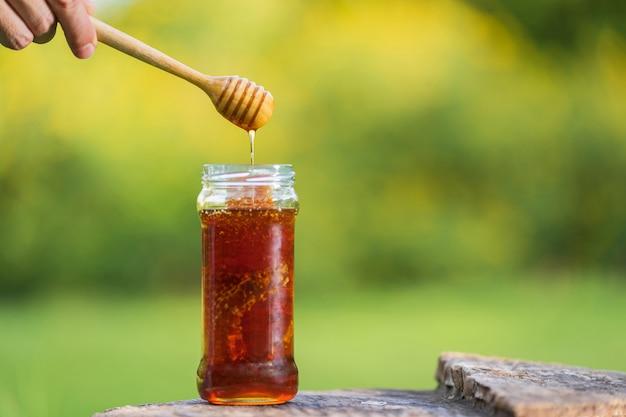 Honig, der vom honigschöpflöffel auf natürlichem hintergrund tropft Premium Fotos