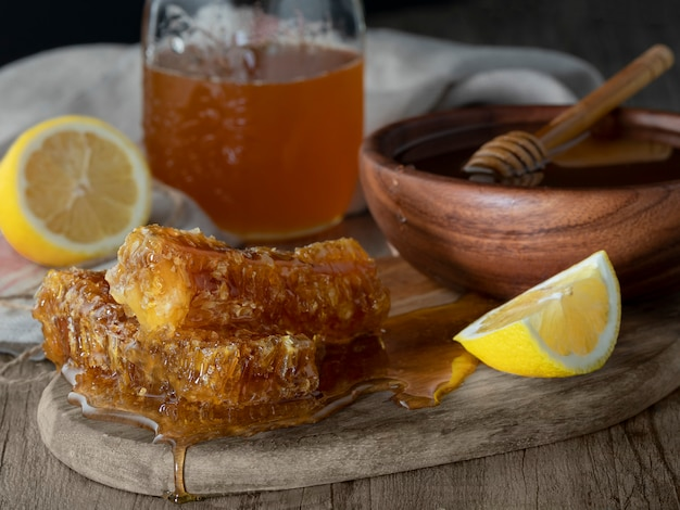 Honig im glas mit bienenwabe und hölzerner drizzler mit zitrone auf holztisch. dunkler hintergrund Premium Fotos