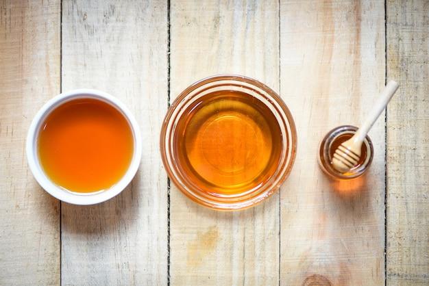 Honig im glas mit hölzernem schöpflöffel auf holz Premium Fotos