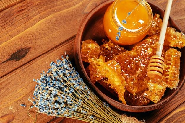Honig im glas mit honigschöpflöffel auf der weinlese hölzern Premium Fotos