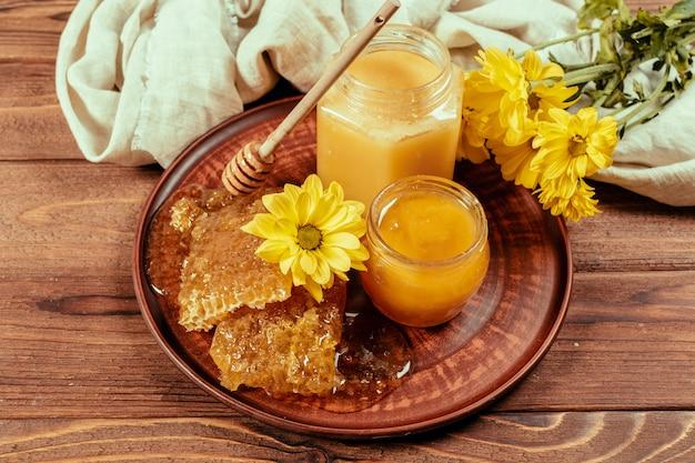 Honig im glas mit honigschöpflöffel auf hölzernem hintergrund der weinlese Premium Fotos