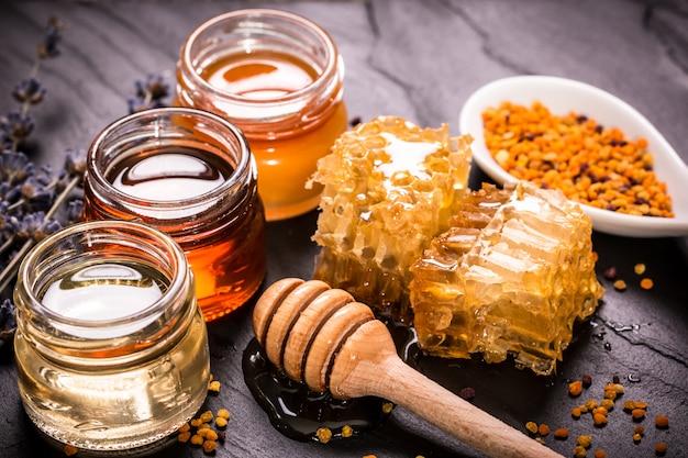 Honig im glas mit honigschöpflöffel auf schwarzem stein Premium Fotos