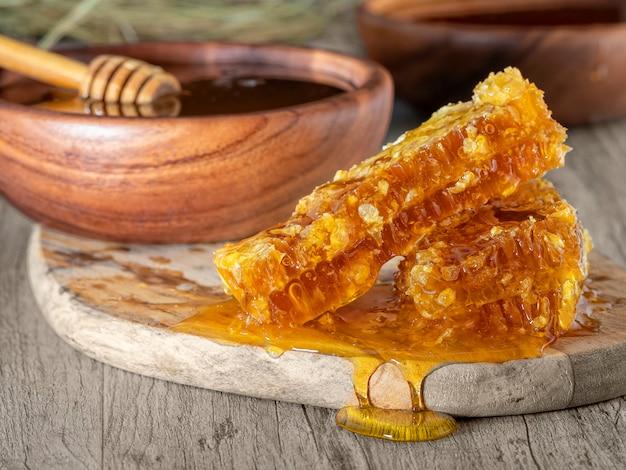 Honig in einer hölzernen schüssel und in einer bienenwabe auf dem tisch. rustikaler stil Premium Fotos