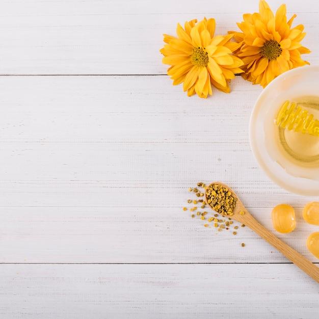 Honig; süßigkeiten; bienenblütenstaub und blumen auf holzoberfläche Kostenlose Fotos