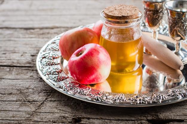 Honig und äpfel auf schönem behälter auf holztischhintergrund. jüdischer feiertag rosh hashanah concept Premium Fotos