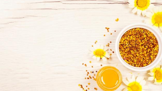 Honig- und bienenpollen mit schöner blume auf weißem hölzernem schreibtisch Premium Fotos