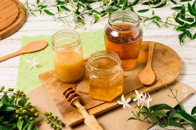 Honiggläser auf tabelle mit blättern Kostenlose Fotos