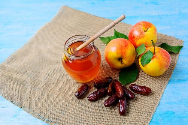 Honigglas, -daten und -äpfel auf blauem hölzernem hintergrund Premium Fotos