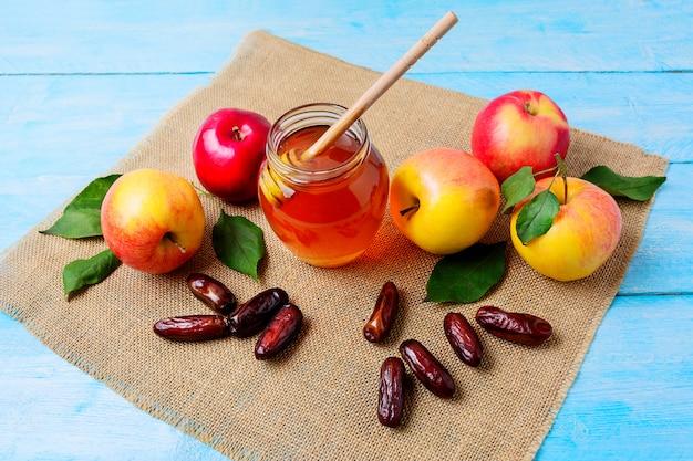 Honigglas, datteln und äpfel auf leinwandserviette Premium Fotos