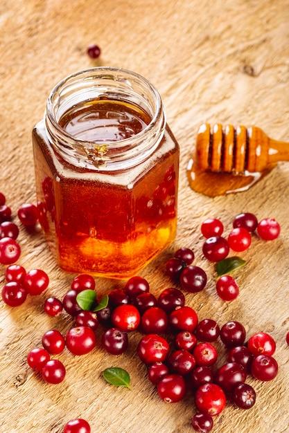 Honigglas des hohen winkelschöpflöffels und rote früchte Kostenlose Fotos