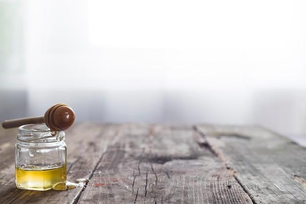 Honigglas mit einem hölzernen stock lässt honig auf einem alten hölzernen hintergrund über hellem fenster ab Premium Fotos