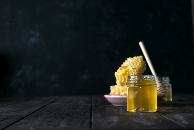 Honigglas mit einem hölzernen stock lässt honig auf einem dunklen hintergrund ab Premium Fotos
