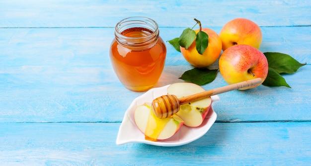 Honigglas- und -apfelscheiben mit honig auf blauem hölzernem hintergrund Premium Fotos