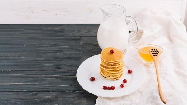 Honigschale; milchglas und gestapelte pfannkuchen auf teller über dem hölzernen hintergrund Kostenlose Fotos
