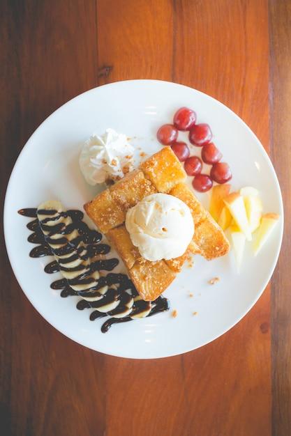 Honigtoast mit vanilleeis, schlagsahne und schokoladensirup. Premium Fotos