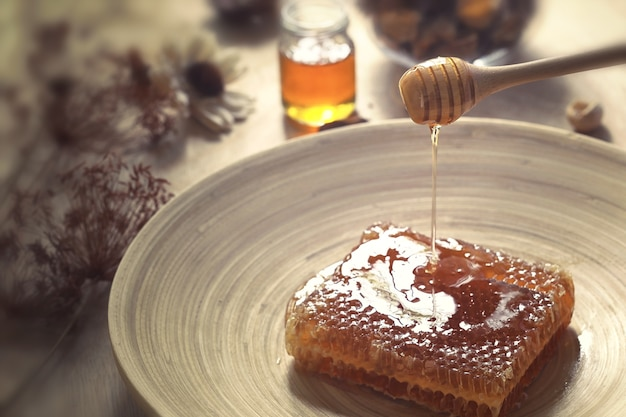 Honigtöpfe mit waben auf einem holztisch mit blumen Premium Fotos