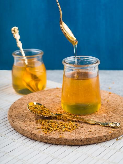 Honigtopf mit bienenpollen auf löffel über dem korkenuntersetzer Kostenlose Fotos