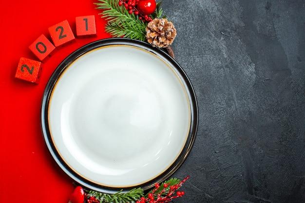 Horizontale ansicht des neujahrshintergrunds mit tafeltellerdekorationszubehörtannenzweigen und -zahlen auf einer roten serviette auf einem schwarzen tisch Kostenlose Fotos