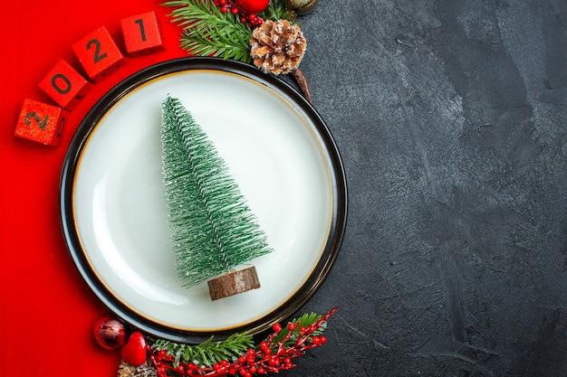 Horizontale ansicht des neujahrshintergrunds mit weihnachtsbaum-abendessenplatte-dekorationszubehör-tannenzweigen und -nummern auf einer roten serviette auf einem schwarzen tisch Kostenlose Fotos