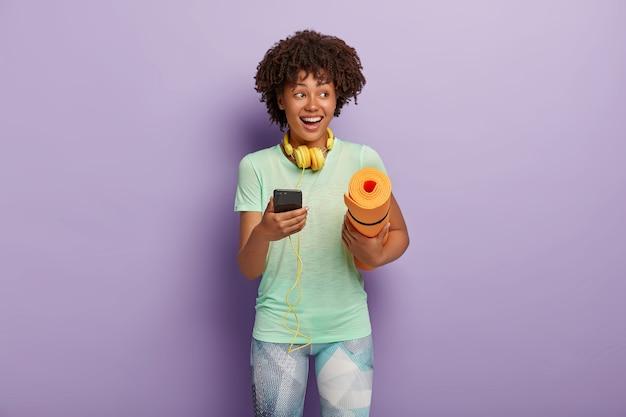 Horizontale aufnahme der glücklichen lockigen fitnessfrau hört musik über kopfhörer und smartphone während des trainings, trägt aufgerolltes karemat, gekleidet in t-shirt und leggings. menschen, die das konzept ausüben Kostenlose Fotos