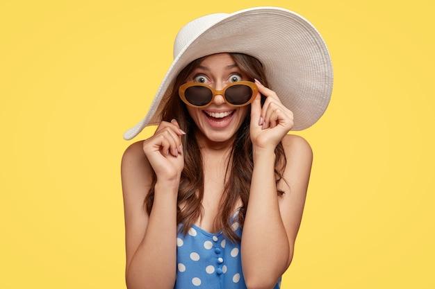Horizontale aufnahme der hübschen attraktiven frau mit dunklem haar, sieht mit überraschung und glück aus, hält hand am rand der schatten, modelle im sommeroutfit über gelber wand. schönheits- und emotionskonzept Kostenlose Fotos