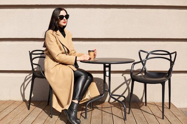 Horizontale aufnahme der jungen frau mit tasse trinkt kakao an der stadtstraßencaféterrasse, sitzt am tisch und träumt, dame trägt beigen mantel Premium Fotos