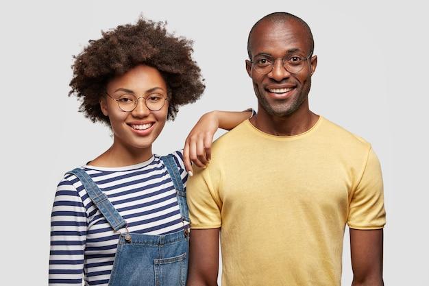 Horizontale aufnahme des erfreuten jungen afroamerikanischen mannes und der frau haben sanftes lächeln Kostenlose Fotos