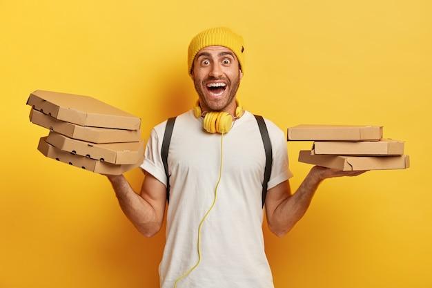 Horizontale aufnahme des glücklichen mannes hält zwei stapel kartons mit pizza, hat freudigen ausdruck überrascht, arbeitet als kurier im lokalen restaurant Kostenlose Fotos