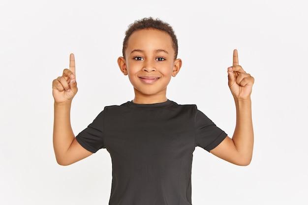 Horizontale aufnahme des hübschen sportlichen afroamerikanischen jungen im stilvollen schwarzen t-shirt, das lokal mit den angehobenen vorderfingern aufwirft, die zeigefinger nach oben zeigen und kopienraum für ihre informationen zeigen Kostenlose Fotos