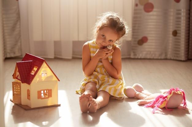 Horizontale aufnahme des kleinen mädchens, das ihr lieblingsspielzeug umarmt und zu hause spielt. kaukasisches kind, das gelbes kleid trägt und traurigen gesichtsausdruck hat. kindheit, wohnkomfort, freundschaftskonzept. Premium Fotos