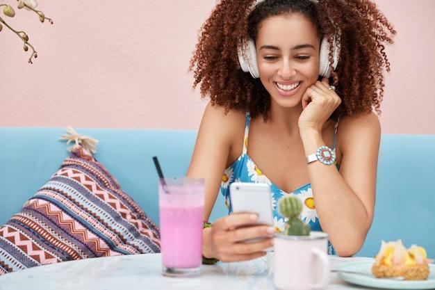 Horizontale aufnahme einer erfreuten dunkelhäutigen afroamerikanischen frau hört musik von der radio-website, die mit dem drahtlosen internet verbunden ist Kostenlose Fotos
