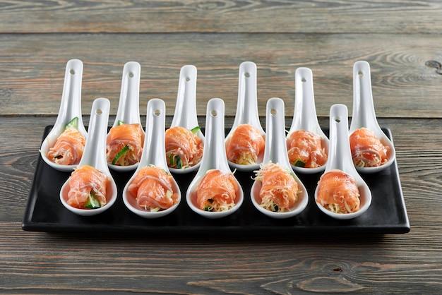 Horizontale aufnahme einer platte mit lachs und käse serviert in großen portionslöffeln delikatesse köstliche leckere vorspeise essen restaurant café luxus lebensstil geräucherten fisch konzept. Kostenlose Fotos