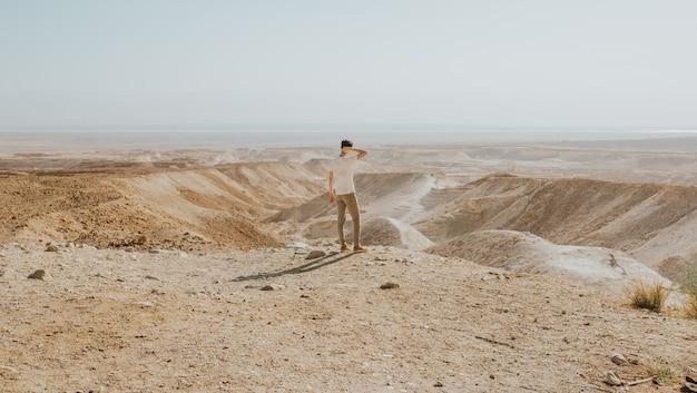 Horizontale aufnahme eines mannes mit einem weißen hemd, das am rand eines berges steht, der die ansicht genießt Kostenlose Fotos