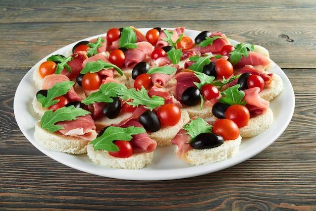 Horizontale aufnahme eines tellers mit häppchen mit schinken-kirschtomaten und schwarzen oliven, verziert mit rucola-rucoli-pflanze, essbarem gemüse, speck-jamon-vorspeisen-menü-restaurant. Kostenlose Fotos