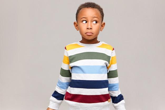 Horizontale aufnahme eines verwirrten lustigen afroamerikanischen jungen in einem gestreiften pullover, der mit ahnungslosem gesichtsausdruck wegschaut und sich schuldig fühlt, weil er alle süßigkeiten aß und vorgab, unschuldig zu sein. ich weiß es nicht Kostenlose Fotos