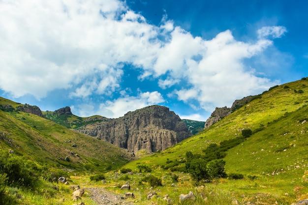 Horizontale aufnahme von bergen bedeckt in grün unter dem schönen bewölkten himmel Kostenlose Fotos