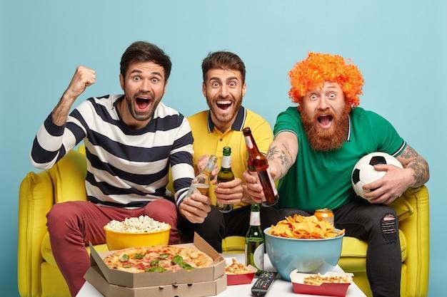 Horizontale aufnahme von freudigen drei männern treffen sich am wochenende, um fußballspiel zu sehen, gefeiertes tor zu erzielen, auf gelbem sofa zu sitzen, isoliert über blauer wand. menschen, aufregungskonzept Kostenlose Fotos