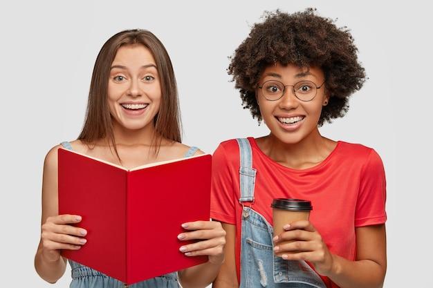 Horizontale aufnahme von fröhlichen zwei interracial studenten lesen buch, lernen material für bevorstehende prüfung, trinken heißen kaffee zum mitnehmen Kostenlose Fotos