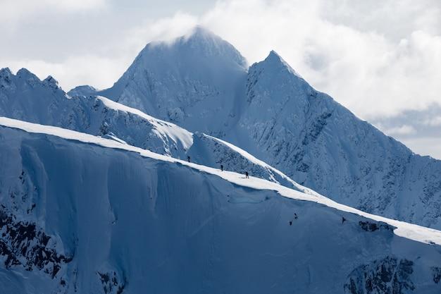 Horizontale aufnahme von hohen bergen bedeckt mit schnee unter weißen wolken und einer gruppe von menschen, die wandern Kostenlose Fotos