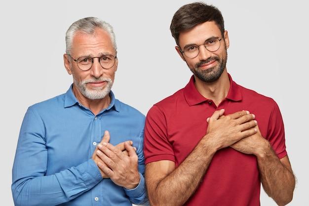 Horizontale aufnahme von zwei zufriedenen männern unterschiedlichen alters, dankbarkeitsgeste, dankbarkeit gegenüber großzügigen menschen, erfreuliche gesichtsausdrücke, isoliert über weißer wand. generation, körpersprache Kostenlose Fotos