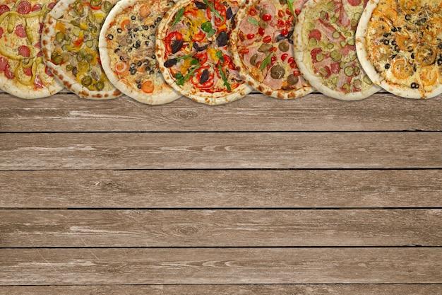 Horizontale collage von verschiedenen gebackenen pizzas auf dunklem holztisch. ansicht von oben. Premium Fotos