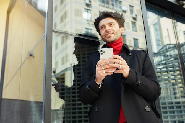 Horizontaler schuss des fröhlichen jungen gutaussehenden dunkelhaarigen unrasierten mannes, der gern nach vorne schaut, während er smartphone in erhöhten händen hält, lokalisiert über stadthintergrund Kostenlose Fotos
