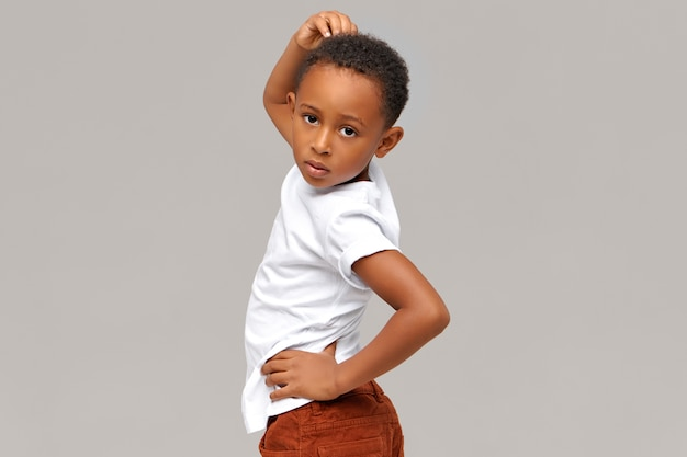 Horizontales bild des hübschen lustigen achtjährigen dunkelhäutigen kleinen jungen, der isoliert vorgibt, modemodell zu sein, Kostenlose Fotos
