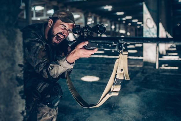 Horizontales bild des soldaten sitzt aus den grund auf einem knie nahe spalte und schreit. er zielt. guy benutzt dafür ein gewehr. er schaut durch die linse des gewehrs. Premium Fotos