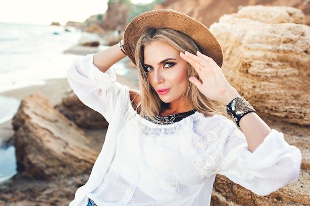 Horizontales porträt des attraktiven blonden mädchens mit den langen haaren, die zur kamera am verlassenen strand aufwerfen. sie schaut in die kamera. Kostenlose Fotos